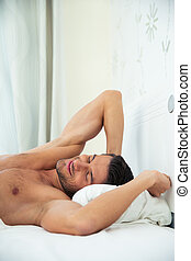 Man resting on the bed at home