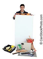 Man resting spirit-level on top of blank poster