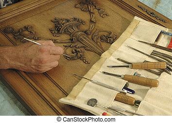 Man restoring antique oak cabinet door with variety of tools
