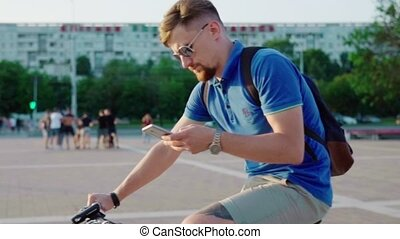 man rides a bicycle and uses a smartphone