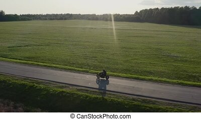 Man rides a motorcycle on a sunset country road Aerial dron...