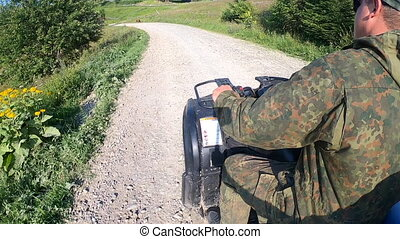 Man rides quad bike on dirt road at top of mountain. Person driving an ATV on ground land. Fast travel by transport on roads. Mountain landscapes and views on summer sunny day. POV. Danger activity