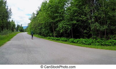 Man rides a skateboard on the road 4k - Rear view of man...