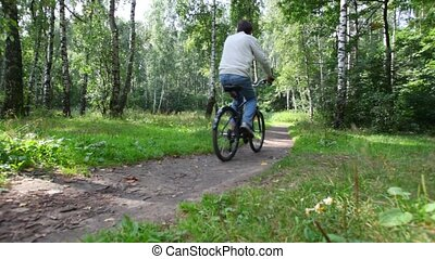 man rides bicycle in forest