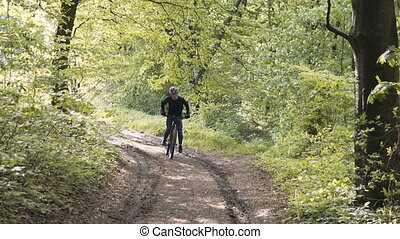 Man Rides Bicycle in the Forest