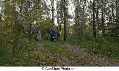 Man rides in the evening in the park on a bicycle.