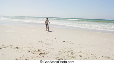Man riding a bicycle at beach on a sunny day 4k