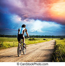 Man Riding a Bike on Country Road at Sunset