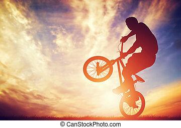 Man riding a bmx bike performing a trick against sunset sky