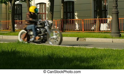 man riding a chopper on a street - motorcyclist in a leather...