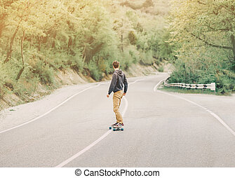Man riding a longboard on mountain road - Young man riding a...