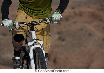 The torso of a man riding a mountain bike in a desert landscape. Horizontal shot.
