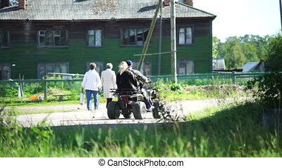 Man riding ATV bike in a village