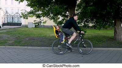 Man riding bicycle with child in safety seat