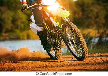 man riding enduro motorcycle on dirt field