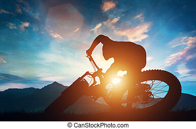 Man riding his bike in mountains during sunset.