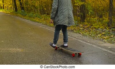 Man riding on a longboard skate on a road through a forest.