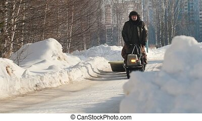 Man riding on crawler mini snowmobile with a trailer and a passenger on a winter road