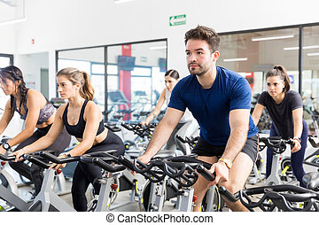 Man Riding Stationary Bicycle With Friends In Gym