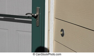 Man Ringing Front Door Bell - Closeup view of an exterior...