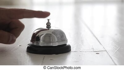 Man ringing hotel reception bell, male hand pushing...
