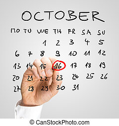 Man ringing the 16th of November on a handwritten calendar for October in red with a marker as a reminder that it is World Food Day and an important event for him.