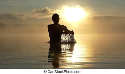 Man rise his hands from the water at sunset in slow motion....