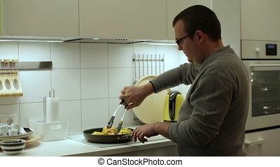 Man roasting chicken in the frying pan