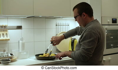 Man roasting chicken in the frying pan