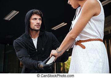 Man robber in hoodie stealing woman bag in the city