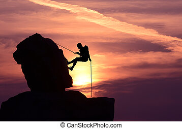 Man rock climber silhouette over bright sunset - Silhouette...