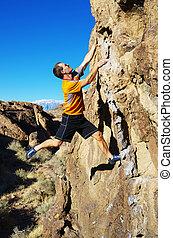 man rock climbing a boulder