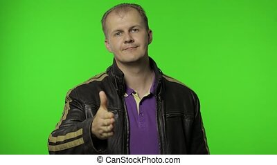 Friendly positive happy rocker man outstretching hand to camera, offering handshake, greeting with kind smile, welcoming showing solidarity, trust concept. Guy biker posing on chroma key background
