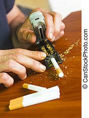 Man rolling cigarettes using fresh tobacco