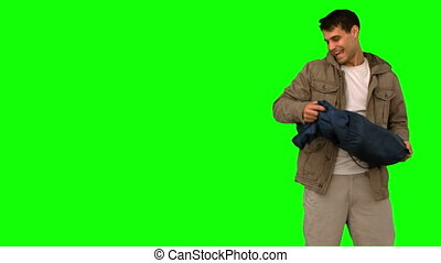 Man rolling out his sleeping bag on green screen in slow...