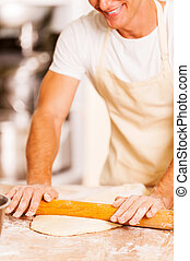 Man rolling out the dough. Close-up of cheerful young baker rolling out the dough with rolling pin
