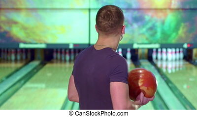 Man rolls the bowling ball