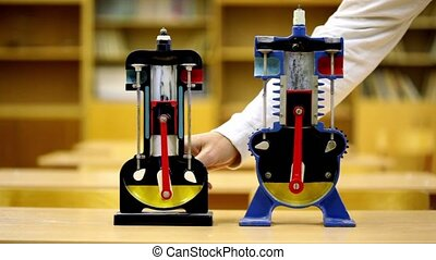Man rotates each of two models of internal combustion engine on desk