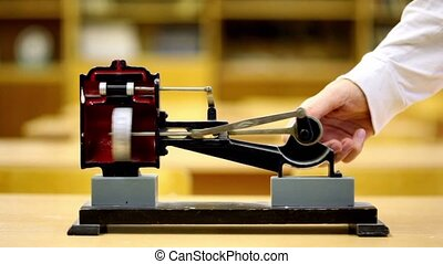 Man rotates model of steam engine on yellow desk in physics school class