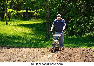 Man rototilling garden - Adult male rototilling the garden