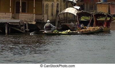 Man rowing canoe full of vegetavles - Wide shot of a man ...