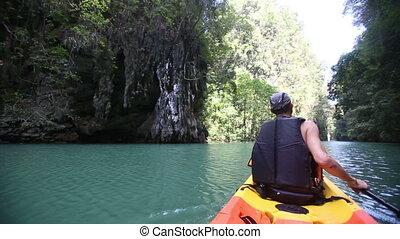 man rowing kayak across sea water