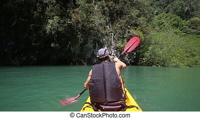 man rowing kayak and waving paddle