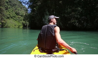 man rowing kayak on green sea water