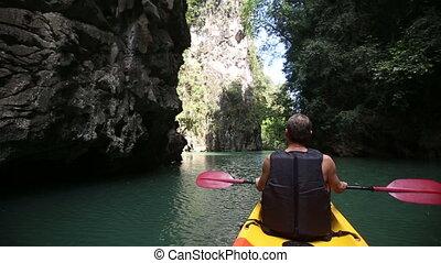 man rowing kayak swim down the river