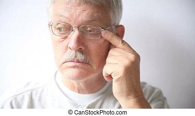 senior man takes off his glasses to rub his very tired eyes