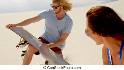 Man rubbing sand over the sand board while woman watching 4k