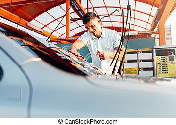 Man rubbing vehicle with car polish after washing....
