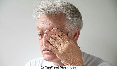man rubs his tired eyes