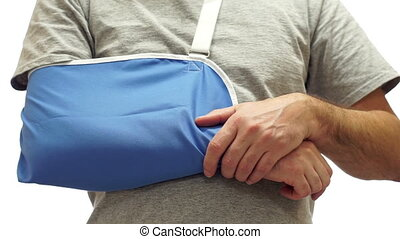 Man Rubs Sore Arm in Medical Sling - Anonymous man isolated...